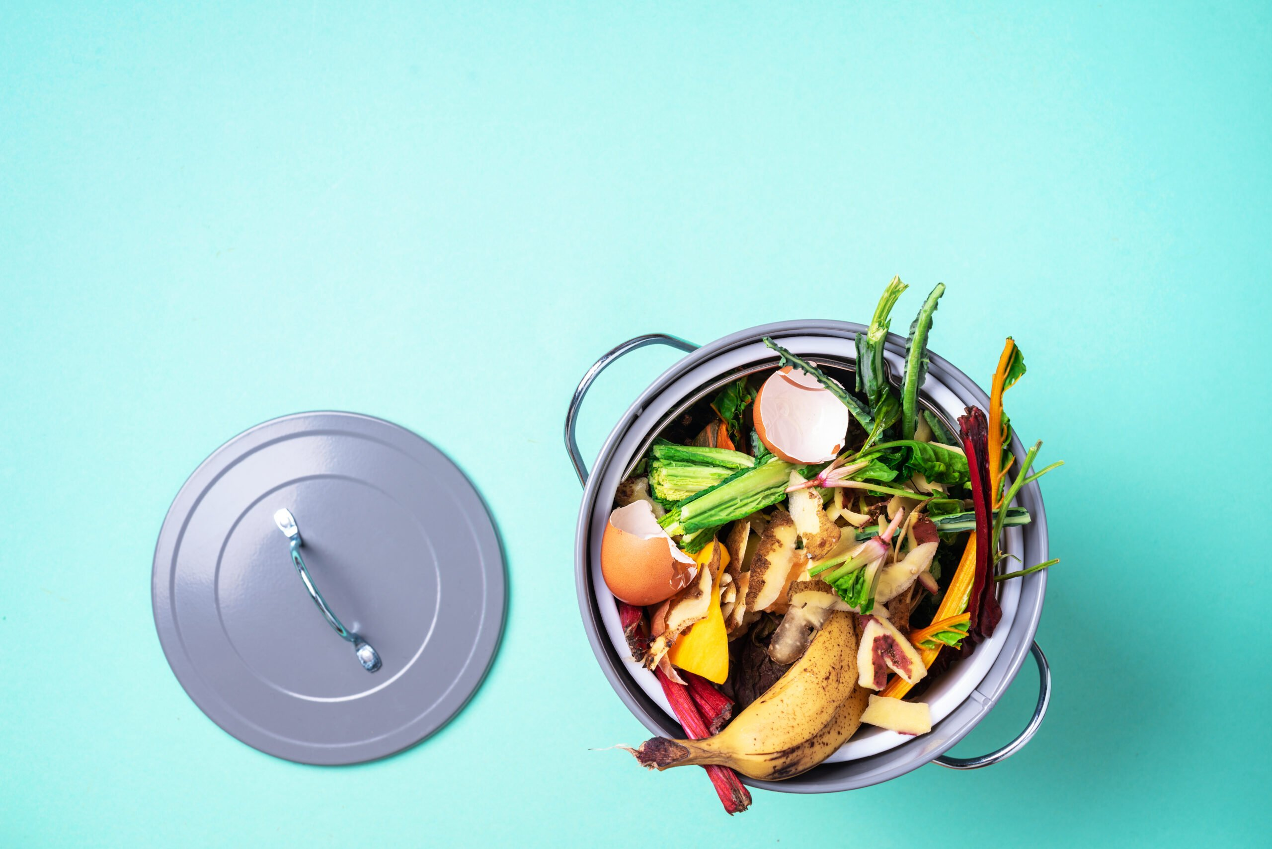 Peeled vegetables on chopping board, white compost bin on blue background. Top view of kitchen food waste collected in recycling compost pot.