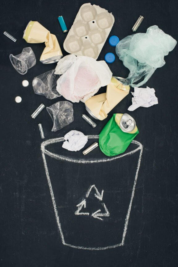 various types of trash falling into drawn trash bin with recycle sign on chalkboard